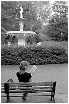 Woman reading a book in front of Forsyth Park Fountain. Savannah, Georgia, USA (black and white)