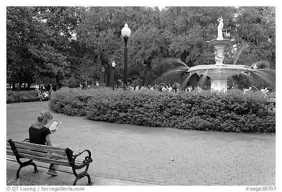 Forsyth Park Fountain with woman sitting on bench with book. Savannah, Georgia, USA
