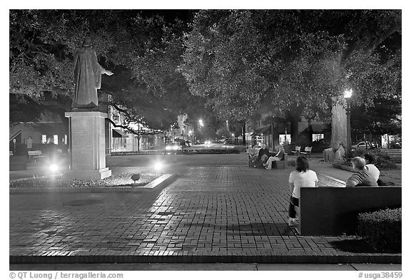 Square by night with people sitting on benches. Savannah, Georgia, USA (black and white)