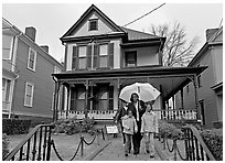 African American family with umbrella in front of Birth Home of Martin Luther King Jr. Atlanta, Georgia, USA ( black and white)