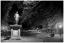 Park with statue and couples sitting on public benches at night. Charleston, South Carolina, USA ( black and white)