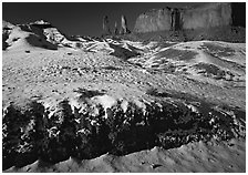 Snow on the floor, with Three Sisters in the background. Monument Valley Tribal Park, Navajo Nation, Arizona and Utah, USA ( black and white)
