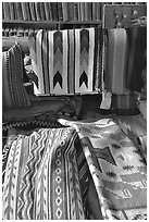 Stacks of varicolored blankets and rugs weaved by Navajo Indians. Hubbell Trading Post National Historical Site, Arizona, USA ( black and white)