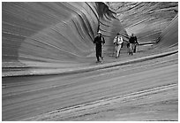 Hikers walk out of the Wave. Coyote Buttes, Vermilion cliffs National Monument, Arizona, USA ( black and white)