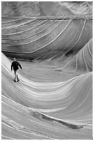 Hiker balances himself in the Wave. Coyote Buttes, Vermilion cliffs National Monument, Arizona, USA (black and white)