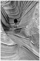 Hiker with backpack on a side formation of the Wave. Coyote Buttes, Vermilion cliffs National Monument, Arizona, USA ( black and white)