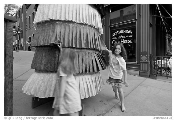 Girls spin tibetan prayer wheel. Telluride, Colorado, USA (black and white)