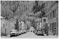 Historic brick buildings and slope with newly leafed aspens. Telluride, Colorado, USA (black and white)