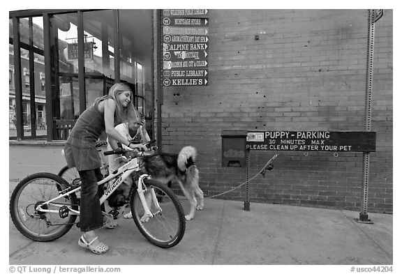 Girls on bikes and puppy parking. Telluride, Colorado, USA (black and white)