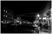 People walking by store on Colorado Street by night. Telluride, Colorado, USA ( black and white)