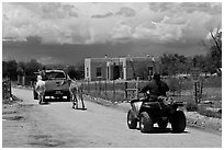 Rural road on the reservation with ATV, truck and horse. Taos, New Mexico, USA (black and white)