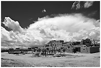 Afternoon cloud hovering over multi-family houses built by Pueblo Indians. Taos, New Mexico, USA (black and white)