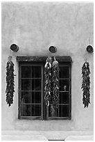 Ristras hanging from vigas and blue window. Taos, New Mexico, USA (black and white)