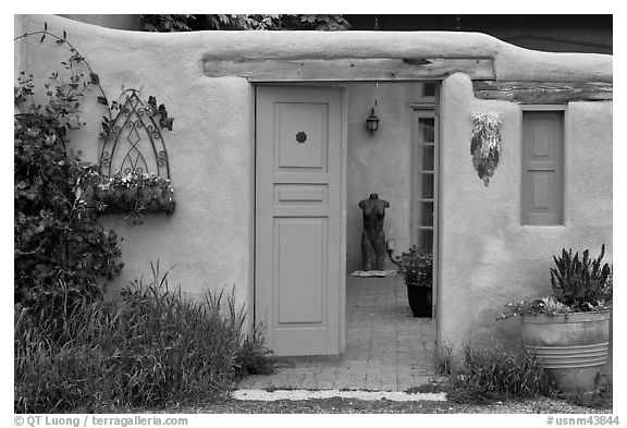 Adobe style walls, blue doors and windows, and courtyard. Taos, New Mexico, USA (black and white)