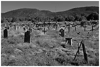 Headstones in grassy area, cemetery, Picuris Pueblo. New Mexico, USA (black and white)