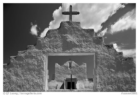 Adobe church framed by entrance in earthen wall, Picuris Pueblo. New Mexico, USA (black and white)