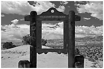 Historic marker framing high desert landscape. New Mexico, USA (black and white)