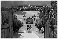 Church framed by doors with roses, Sanctuario de Chimayo. New Mexico, USA ( black and white)