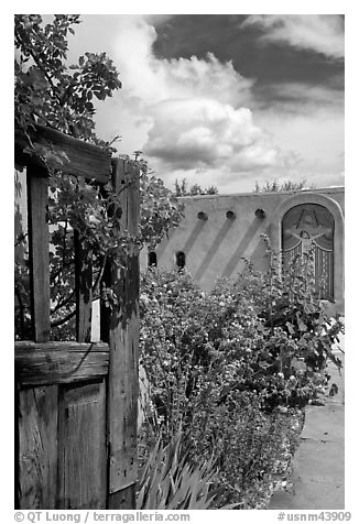 Gardens and adobe wall, Sanctuario de Chimayo. New Mexico, USA