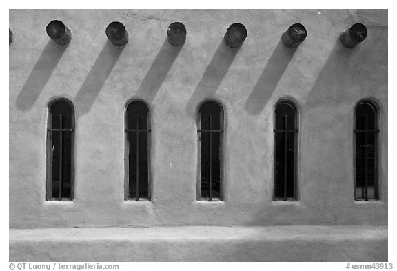 Facade with vigas (heavy timbers) extending through walls to support roof, Chimayo sanctuary. New Mexico, USA (black and white)