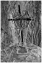 Metal cross festoned with rosaries, and crosses made of twigs, Sanctuario de Chimayo. New Mexico, USA (black and white)