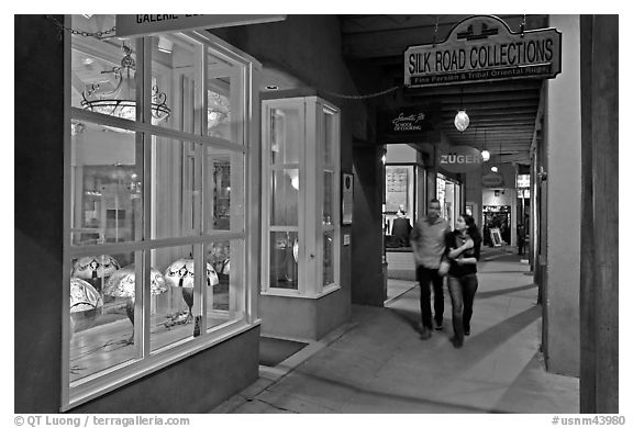 Couple walking by night in front of gallery. Santa Fe, New Mexico, USA (black and white)