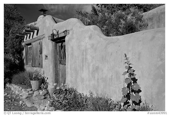 Adobe wall and weathered wooden door and window. Santa Fe, New Mexico, USA