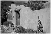 Adobe wall and weathered wooden door and window. Santa Fe, New Mexico, USA (black and white)