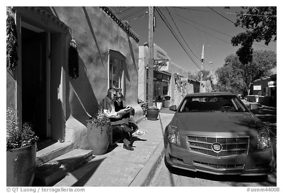 Couple reading art magazine in front of gallery. Santa Fe, New Mexico, USA (black and white)