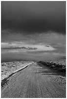 Dirt road under storm clouds. New Mexico, USA ( black and white)