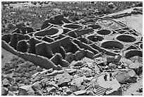 Visitors inspecting the complex room arrangement of Pueblo Bonito. Chaco Culture National Historic Park, New Mexico, USA (black and white)