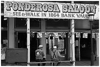 Men sitting on bench below Ponderosa Saloon sign. Virginia City, Nevada, USA (black and white)
