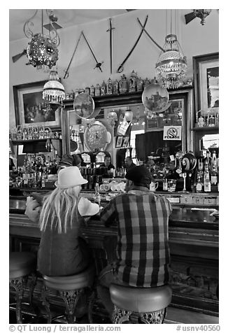 Man and woman sitting in saloon. Virginia City, Nevada, USA (black and white)