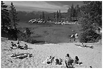 Young people sunbathing on sandy beach, Sand Harbor, Lake Tahoe, Nevada. USA (black and white)