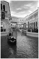 Gondolier singing song to couple during ride inside Venetian casino. Las Vegas, Nevada, USA (black and white)
