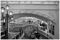 Gondolas passing below bridge, inside Venetian hotel. Las Vegas, Nevada, USA (black and white)