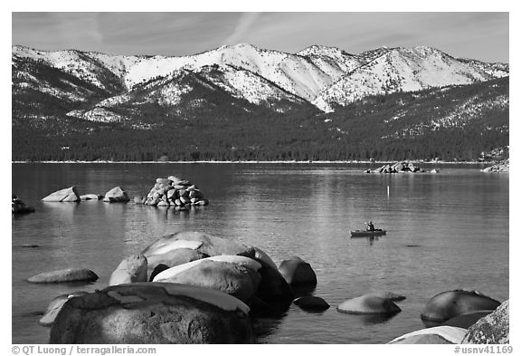 Boulders, kayak, and snowy mountains, Sand Harbor, Lake Tahoe-Nevada State Park, Nevada. USA (black and white)