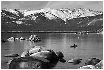 Boulders, kayak, and snowy mountains, Sand Harbor, Lake Tahoe-Nevada State Park, Nevada. USA ( black and white)