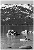 Kayaker with backdrop of snow-covered mountains, Lake Tahoe-Nevada State Park, Nevada. USA ( black and white)