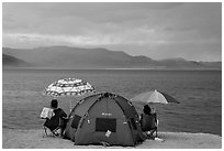 People with tent and beach umbrellas, approaching storm. Pyramid Lake, Nevada, USA (black and white)