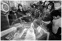 Family plays arcade game with spining lights. Reno, Nevada, USA (black and white)