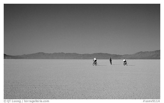 Three bicyclists on the desert Playa, Black Rock Desert. Nevada, USA (black and white)