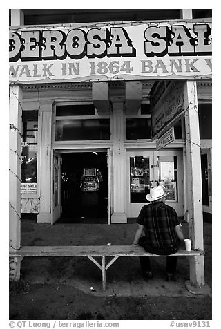 Man with cowboy hat sitting in front of a casino. Virginia City, Nevada, USA (black and white)