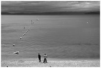 Men standing on beach under dark sky, South Lake Tahoe, California. USA (black and white)