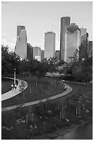 People walking in park with skyline behind. Houston, Texas, USA ( black and white)