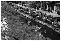 Tables under colorful umbrellas next to canal. San Antonio, Texas, USA ( black and white)