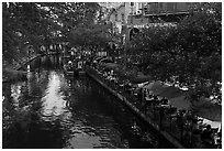 Restaurant tables and barge, Riverwalk. San Antonio, Texas, USA ( black and white)