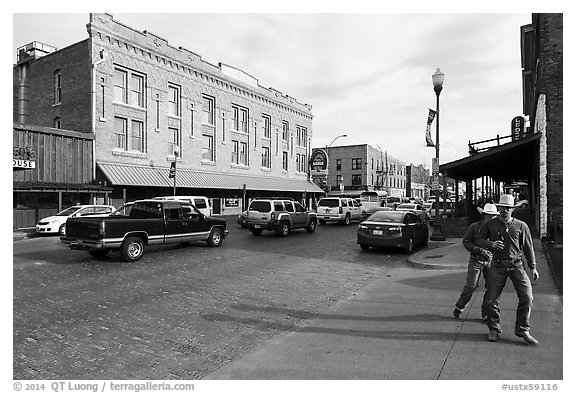 Stokyards street with brick buildings, men with cowboy hats. Fort Worth, Texas, USA (black and white)
