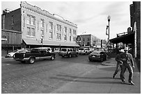 Stokyards street with brick buildings, men with cowboy hats. Fort Worth, Texas, USA ( black and white)