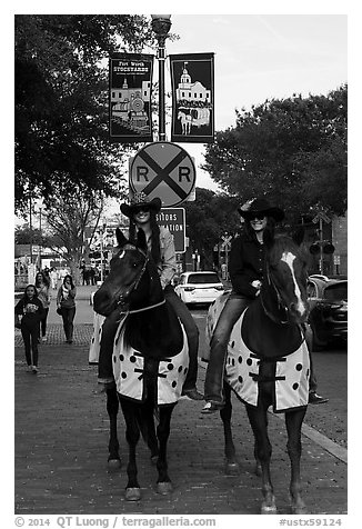 Women riding horses on sidewalk, Stockyards. Fort Worth, Texas, USA (black and white)